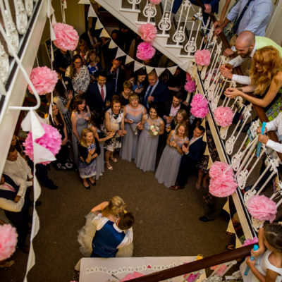 Bride and groom seen from the top of the staircase in the Manor House